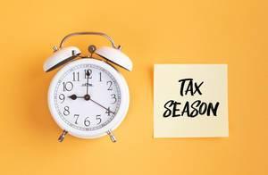Wecker und ein Zettel mit 'Tax season' Text vor gelbem Hintergrund
