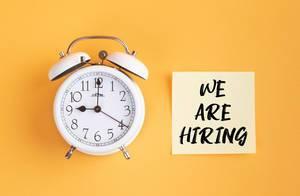 Wecker und ein Zettel mit 'We are hiring' Text vor gelbem Hintergrund