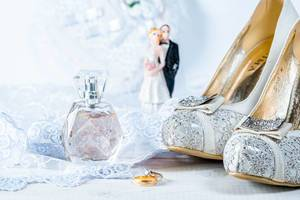 Wedding rings, perfume, shoes and statues of the bride and groom on white background