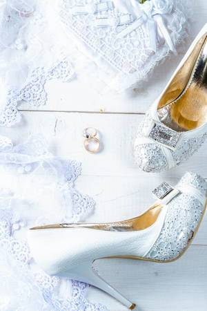 Wedding white bride shoes and rings on white wooden table