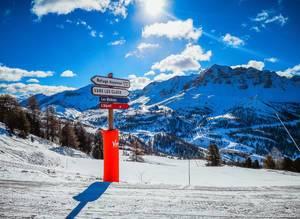 Wegweiser in Skigebiet Vars, Frankreich vor verschneiten Bergen bei Sonnenschein