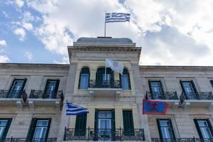 """Wehende Flaggen am Luxushotel und Wahrzeichen """"Poseidonion Grand Hotel"""" in Spetses, Griechenland"""
