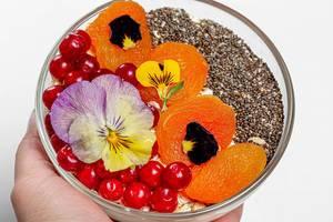 Weibliche Hand hält eine kleine Glasschüssel mit Haferflocken, Beeren, Chiasamen und essbaren Blumen