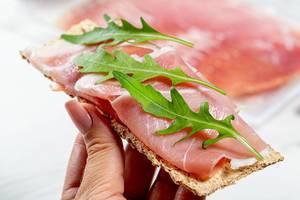 Weibliche Hand hält einen Abonett-Sandwich mit trockengehärtetem Schinken und frischer Rucola