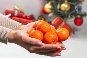 Weibliche Hand hält frische Mandarinen mit einem geschmückten Weihnachtsbaum im Hintergrund