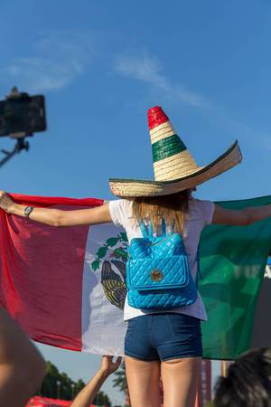 Weiblicher Fußballfan mit Sombrero und mexikanischer Flagge