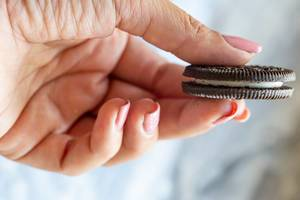 Weiblicher Hand hält einen Oreo Keks mit Vanille Füllung