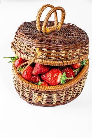 Weidenkorb gefüllt von frischen Erdbeeren mit weißem Hintergrund