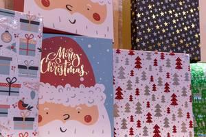 Weihnachtliche Poster mit Geschenken, Weihnachtsbäumen und Sternen verziert