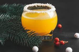 Weihnachtlicher Orangen Cocktail vor Tannenzweigen auf einem schwarzen Hintergrund