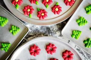 Weihnachts-Plätzchen auf Tellern auf einem Tisch mit Mehl