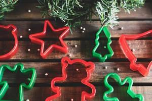 Weihnachts-Plätzchenformen mit Tannenzweigen auf Holz-Untergrund