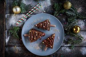 Weihnachts Schokoladenkuchen auf blauem Teller mit Tannenzweigen