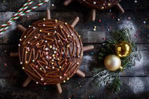Weihnachts Schokoladenkuchen mit Tannenzweigen und goldenen Weihnachtsbaumkugeln auf Holztisch