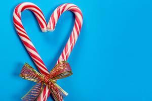 Weihnachts Zuckerstangen in Herzform vor blauem Hintergrund