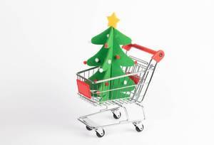 Weihnachtsbaum aus Filzmatte in Einkaufswagen vor weißem Hintergrund steht für Weihnachtseinkäufe