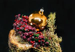 Weihnachtsbaumkugel und weiterer Schmuck vor schwarzem Hintergrund