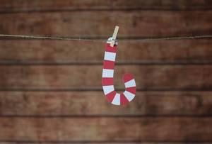 Weihnachtsdeko Zuckerstange hängt an Leine