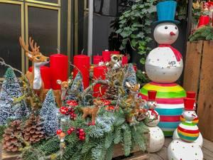 Weihnachtsdekoration mit Tannenzweigen, roten Kerzen, Schneemännern mit rotem Hut und bunten Steifen, Rehen und einem Hirsch, Eule, Tannenzapfen und Fliegenpilzen