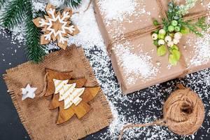 Weihnachtsgeschenk in Naturpapier mit Mistelzweig, Tannenzweig, Holzstern
