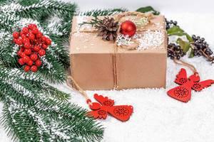 Weihnachtsgeschenk mit Tannenzapfen und Christbaumkugel geschmückt im Schnee mit roten Engeln und Tannenzweigen
