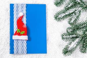Weihnachtsgrußkarte in blau mit Weihnachtsmannmütze im Schnee