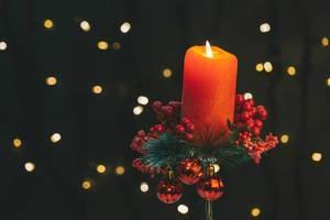 Weihnachtshintergrund mit Bokeh-Effekt und einer geschmückten Adventskerze