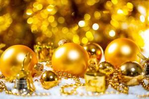 Weihnachtskonzept - goldene Weihnachtsbaumkugeln und Geschenke im Schnee
