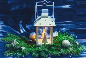 Weihnachtslanterne mit Tannenzweigen auf blauem Hintergund