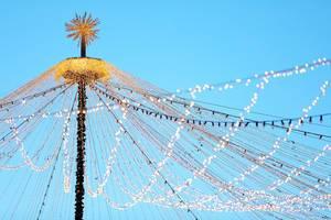 Weihnachtsmarkt Beleuchtung von einem Hauptmast abgehend vor blauem Himmel