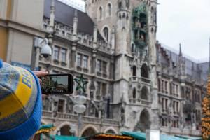 Weihnachtsmarktbesucher benutzt Smartphone für Video von Kölner Dom und Markt