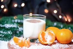 Weihnachtsmotiv - Ein Glas Milch mit Mandarinen und Tannenzweigen im Hintergrund