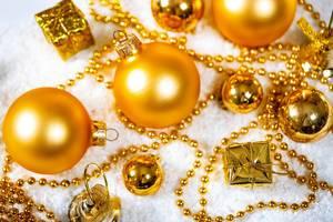 Weihnachtsmotiv - goldene Christbaumkugeln mit Geschenken und Kette im Schnee