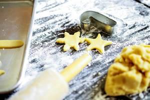 Weihnachtsplätzchen in Sternchenform auf mit Mehl bedecktem Backblech