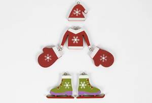 Weihnachtspullover mit Mütze, Fäustlingen und Schlittschuhen aus Holz auf weißem Hintergrund
