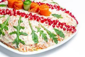Weihnachtssalat dekoriert mit Rucola, Granatapfel-Kernen und Gemüse auf einem weißem Teller auf weißem Hintergrund