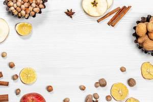 Weihnachtsstimmung: Haselnüsse, Walnüsse, Zimtstangen, Sternanis, Äpfel und getrocknete Früchte in obene Aufnahme