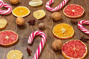 Weihnachtsstimmung: Weihnachtslutscher mit getrockneten Zitrusfrüchten auf einem Holztisch