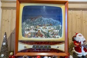 Weihnachtsszene mit verschneitem Dorf auf nostalgischem Fernseher neben Tannenbaum und Nikolaus