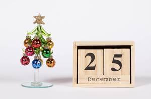 Weihnachtstag 25. Dezember mit Holzkiste dargestellt, daneben Weihnachtsbaum aus Kunststoff mit bunten Weihnachtskugeln