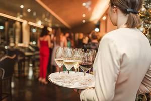 Wein serviert auf einem Tablett von einer Kellnerin in einem Restaurant