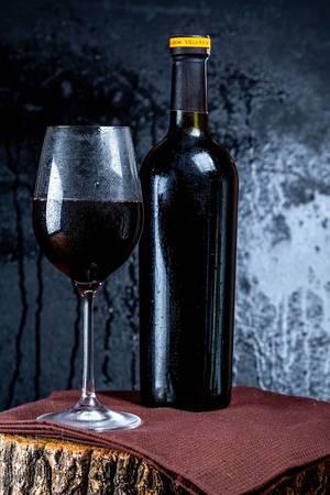 Weinflasche hinter einem eingeschenkten Rotweinglas, auf einem rustikalen Baumstamm, vor schwarzem Hintergrund