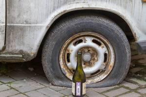 Weinflasche neben einem schrottreifen Auto mit einem Platten