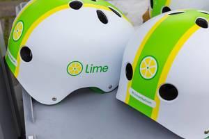 Weiß-grün-gelbe Sturzhelme mit Lime Logo und #LimeNation Hashtag für sichere E-Scooter Fahrten