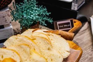 Weißbrot in Scheiben geschnitten auf einem Holzbrett am Frühstücksbüfett