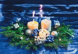 Weiße Adventskerzen auf Tannenzweigen mit silbernen Kugeln auf blauem Hintergrund