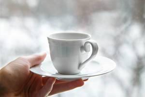 Weiße Kaffeetasse auf Unterteller in Frauenhand