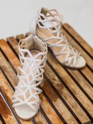 Weiße, moderne Brautschuhe mit Glitzereffekt auf Holztisch