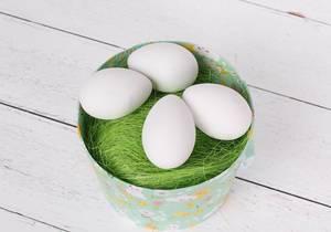 Weiße Ostereier in einem Eimer mit grünem Gras auf einem Holztisch