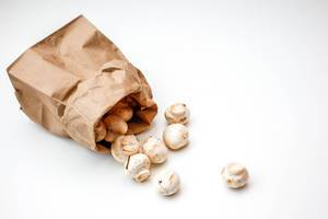 Weiße Pilze in einer Papiertüte
